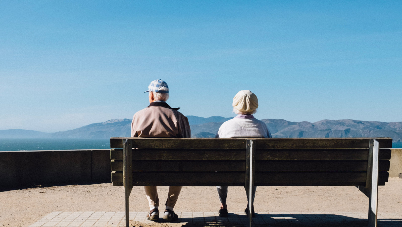 two seniors sitting on a bench looking out at scenery