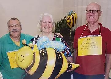 3 seniors posing with a bee balloon