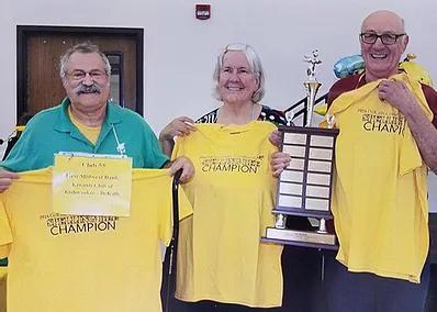 3 seniors holding up event t-shirts